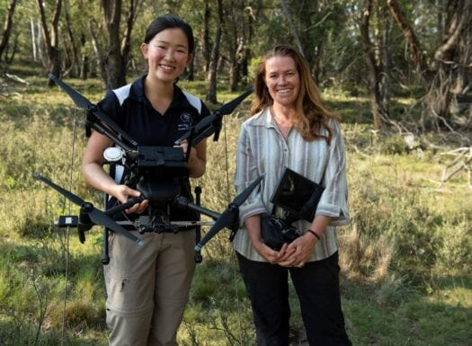 laura is holding a drone and debbie is holding the drone controller as they smile at the camera rosenbergs goannas project