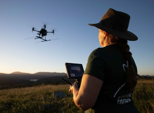 a female drone pilot with her back to the camera holding a drone controller while a drone is up in the air